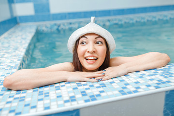 A cheerful Asian woman is swimming in a cold plunge pool after a hot sauna, the concept of strengthening immunity and hardening