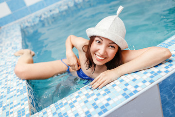 woman in plunge indoors swimming pool, relaxation and hardening of the body concept