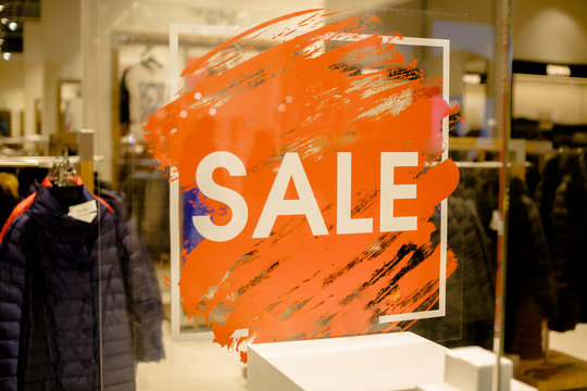 SALE Sign on the shop's window display.discount sign on show window. Sale sign, symbol in clothes shop,The red announcement of a fifty-percentage discount on a glass show-window. Copy space