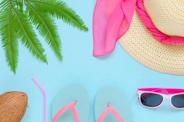 Beach hat, glasses, flip-flops, palm leaf, coconut over blue background.