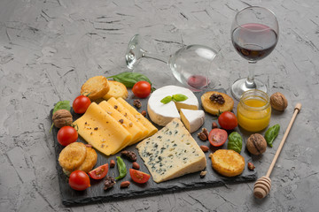 Different kinds of cheeses on a black board, with cherry tomatoes and basil and nuts.With red wine in a glass