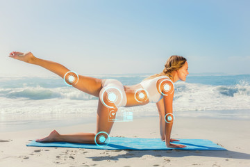 Gorgeous fit blonde in pilates pose on the beach against fitness interface
