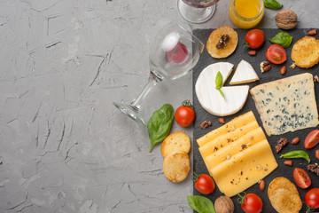 Different kinds of cheeses on a black board, with cherry tomatoes and basil and nuts. And a glass of red wine. A top view, with an empty space for an inscription or advertisement