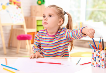 Little cute girl drawing at table indoors