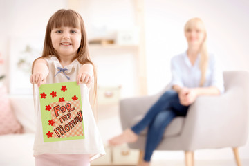 Little girl holding greeting card for Mother's day at home
