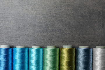 Color sewing threads on gray background, top view