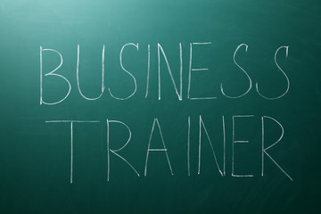 Text BUSINESS TRAINER written on chalkboard. Coaching concept