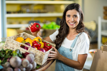 Smiling woman picking bell pepper from the basket from grocery store