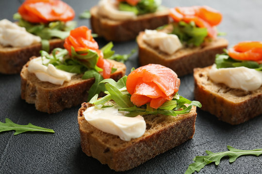 Tasty sandwiches with fresh sliced salmon fillet on table