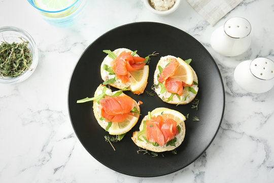 Plate of tasty sandwiches with fresh sliced salmon fillet on table, top view