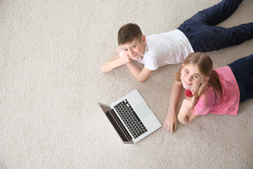 Teenage girl and her brother with laptop lying on cozy carpet at home