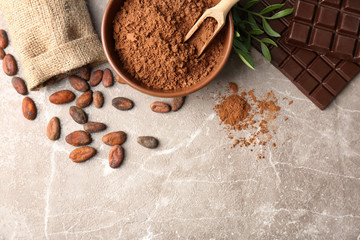 Flat lay composition with cocoa powder, beans and chocolate on light background