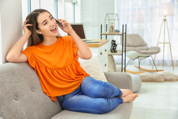 Attractive young woman talking on mobile phone at home