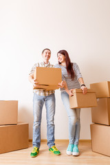 Picture of man and woman standing among cardboard boxes