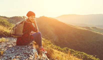 Woman tourist at top of mountain at sunset outdoors during  hike in summer