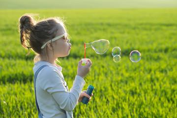 little girl is blowing a soap bubbles, Outdoor Portrait