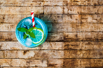 Blue cocktails with lemon on wooden table