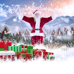 Jolly Santa opens his arms to camera against cute village in the snow