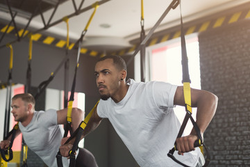 Men performing TRX training in gym