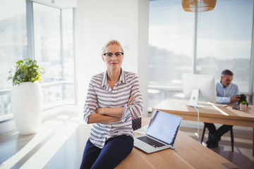 Portrait of confident executive sitting with arms crossed on desk