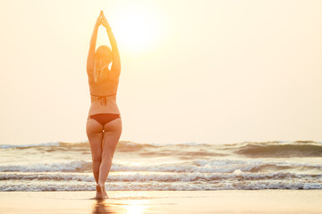 beautiful and young woman practicing meditative yoga on the beach