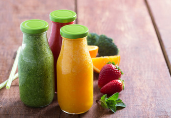Fresh strawberry, orange and broccoli smoothie in bottles with fruits and vegetables on a brown wooden rustic background