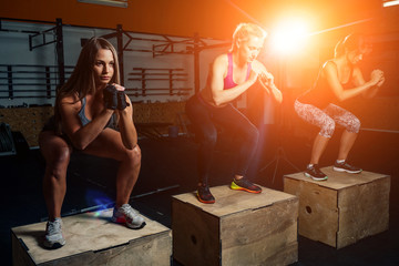 sports girls in the gym teamwork perform exercises for the legs