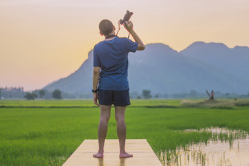 Young man practicing landscape photography before sunset at rice