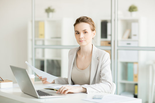Serious female manager looking at you while working with documents and organizing work