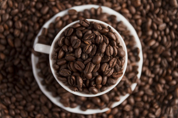 Cup filled with coffee beans on coffee beans background. Selective focus. Top view.
