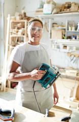 Female carpenter with electric fretsaw looking at camera through protective eyeglasses in workroom