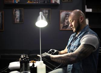 male tattooist putting on black latex gloves preparing for work