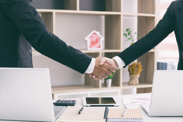 Businessman and businesswoman shaking hands after meeting in office, partnership concept.