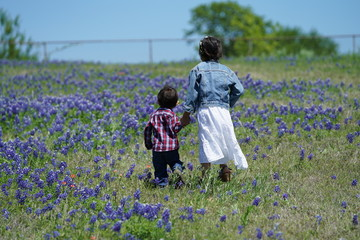 Boy and girl walking along Texas Bluebonnets trail during spring time around the Texas Hill Country