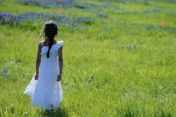 Girl standing along Texas Bluebonnets trail during spring time around the Texas Hill Country