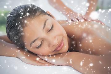 Beautiful brunette enjoying a massage  against snow falling