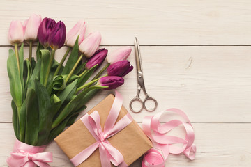Colorful tulips on white wooden background, top view