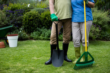 Low section of senior couple standing with garden tools