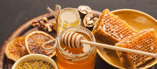 In de dag Bee Various types of honey on wooden platter, closeup