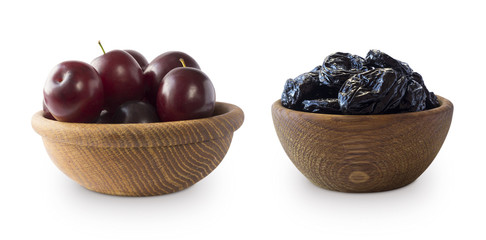 Fresh plums and dried prunes isolated on a white background. Dried prunes and fresh plums in a bowl on white background. Dried prunes and plums with copy space for text.