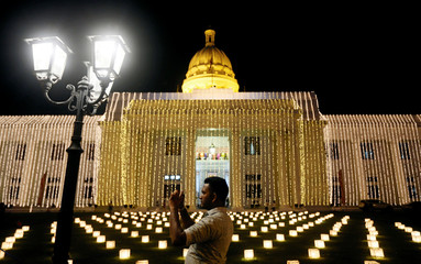 A man takes a picture of decorations at the Vesak celebrations zone to commemorate the birth, enlightenment and death of Buddha at a temple, in Colombo