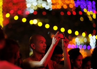 A Buddhist monk takes pictures of a Vesak lantern at the Vesak celebrations zone to commemorate the birth, enlightenment and death of Buddha at a temple, in Colombo