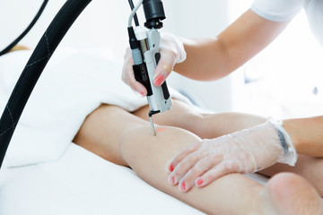 The beautician's hands removing leg hair with a laser to her client in the beauty salon.