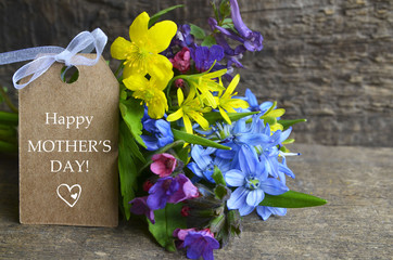 Happy Mother's Day greeting card with spring flowers bouquet on old wooden background.