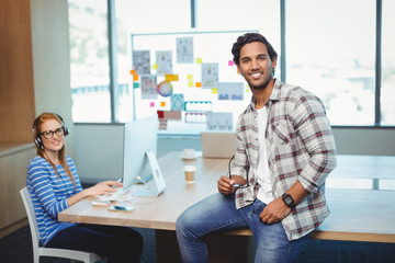 Male graphic designer sitting on desk with coworker in conference room
