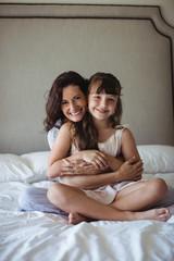 Smiling mother embracing her daughter in bedroom