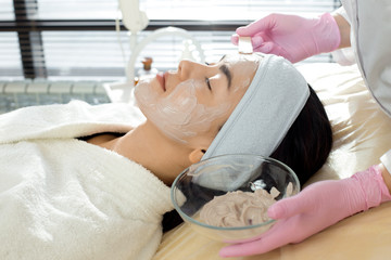 Side view closeup of  female cosmetologist applying facial mask to face of beautiful young woman lying on massage table during beauty treatment in SPA salon