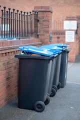 row of black and blue wheelie bin against a brick wall in the UK