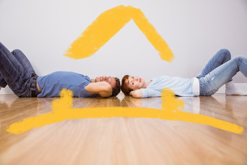 Couple lying on the floor against house outline