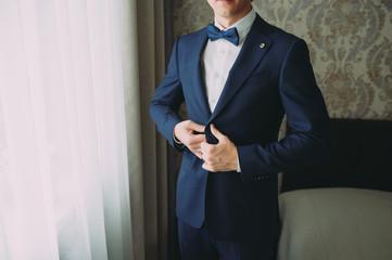 stylish groom in a blue suit posing. wedding preparations